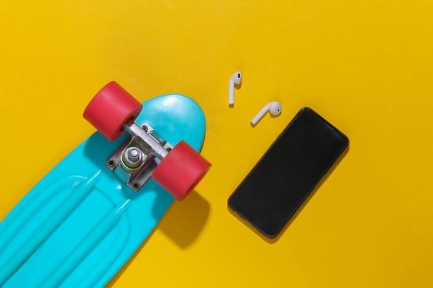 Tavola da crociera, smartphone e cuffie wireless su uno sfondo giallo brillante. accessori per la gioventù, outfit hipster.