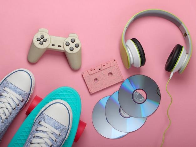 Scheda cruiser, cuffie stereo, cassetta audio, dischi cd, gamepad su superficie rosa