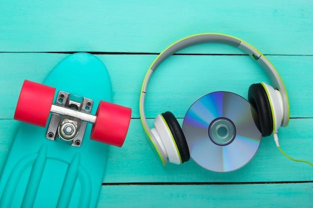Bordo dell'incrociatore e cuffie stereo con disco cd su superficie di legno blu
