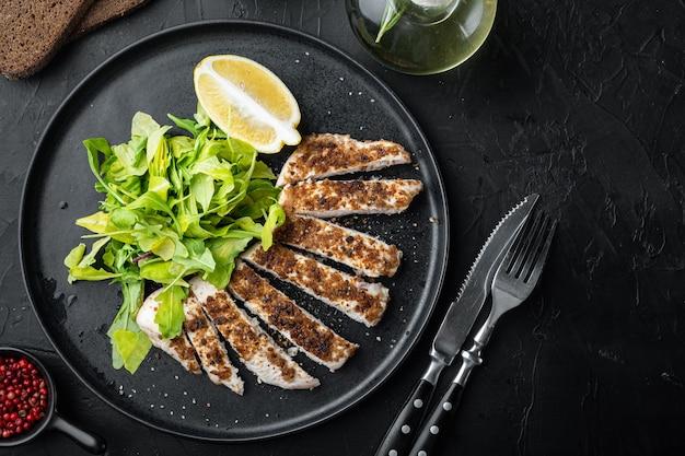 Filetto di petto di pollo sbriciolato alla griglia, su tavola nera, piatto