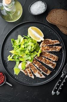 Filetto di petto di pollo sbriciolato alla griglia, sulla tavola nera, vista dall'alto