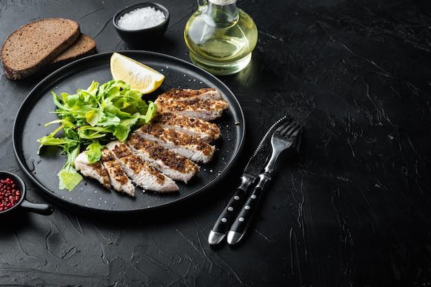 Filetto di petto di pollo sbriciolato alla griglia, sulla tavola nera
