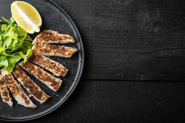 Filetto di petto di pollo sbriciolato alla griglia, su un tavolo di legno nero, piatto