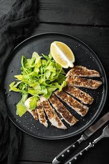 Filetto di petto di pollo sbriciolato alla griglia, su un tavolo di legno nero, vista dall'alto