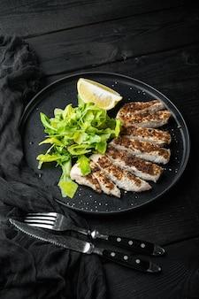 Filetto di petto di pollo sbriciolato alla griglia, su un tavolo di legno nero