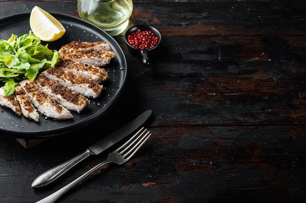 Filetto di petto di pollo sbriciolato alla griglia, su tavola di legno
