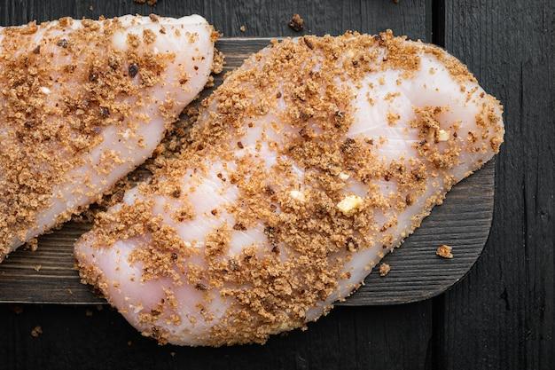 Ingrediente di petto di pollo crudo sbriciolato, su fondo di legno nero, piatto