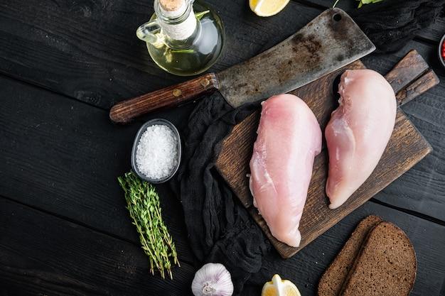 Petto di pollo crudo sbriciolato ingrediente con coltello da macellaio su tavolo di legno nero, piatto disteso