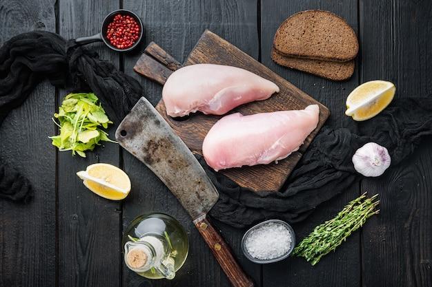 Petti di pollo crudi sbriciolati ingrediente con coltello da macellaio su tavolo di legno nero, vista dall'alto