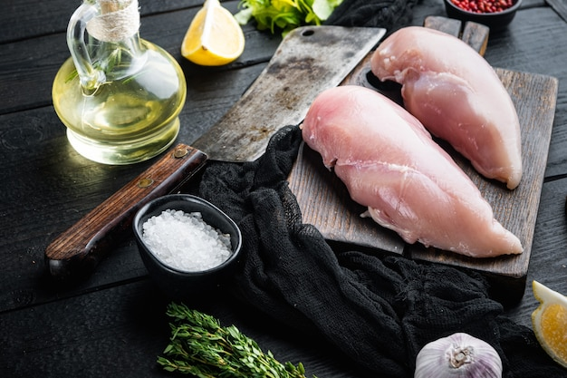Ingrediente di petti di pollo crudi sbriciolati con coltello da macellaio sul tavolo di legno nero