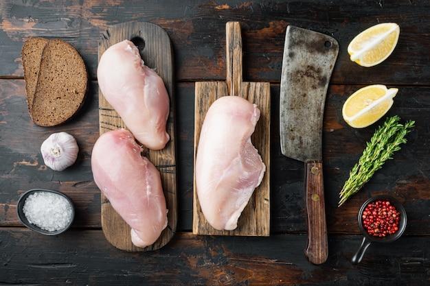 Ingrediente di petti di pollo crudi sbriciolati con coltello da macellaio, sul tavolo di legno scuro, vista dall'alto