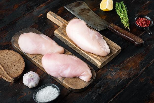 Ingrediente di petti di pollo crudo sbriciolato con coltello da macellaio, sul tavolo di legno scuro