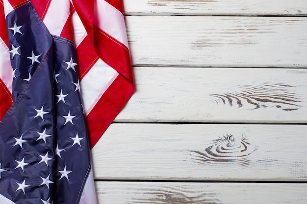 Bandiera americana spiegazzata. bandiera americana su fondo in legno. banner posa sul tavolo bianco. democrazia e libertà.