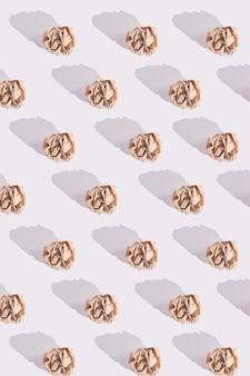 Modello di palline di carta artigianale marrone sgualcito con ombre dure sul bianco