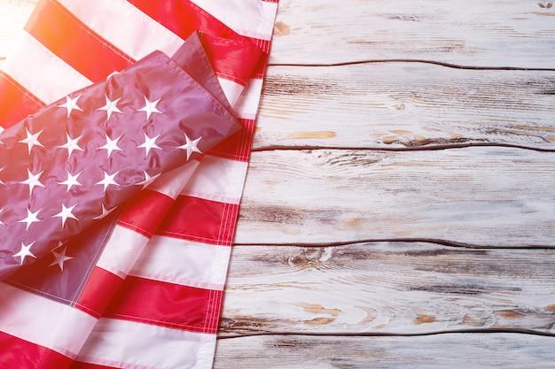 Bandiera degli stati uniti spiegazzata. bandiera degli stati uniti su fondo di legno. bandiera nazionale alla luce del sole. pace, amore e prosperità.