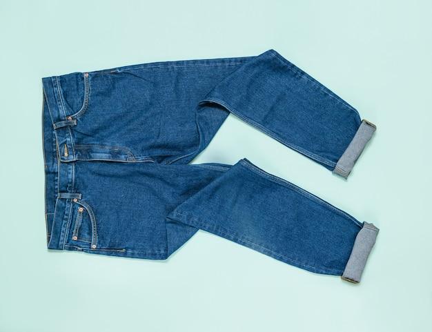 Jeans da uomo sgualciti con polsini su sfondo blu. abbigliamento da uomo in denim alla moda. lay piatto. la vista dall'alto.