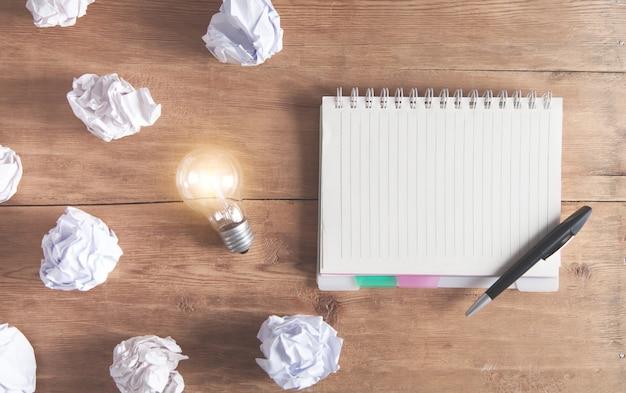 Documenti sgualciti con un blocco note e una penna sulla scrivania in legno.