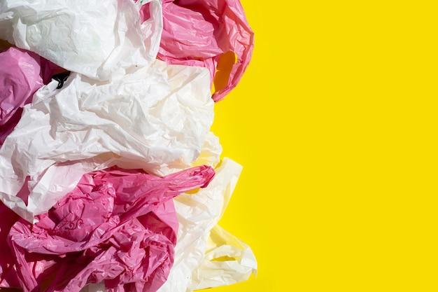 Sacchetti di plastica sgualciti sulla superficie gialla
