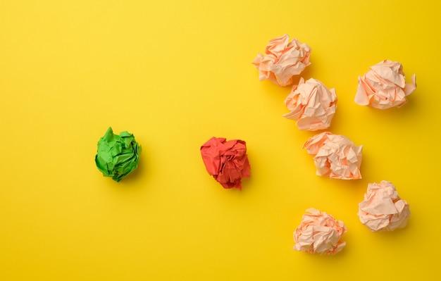 Fogli spiegazzati di carta colorata su una superficie gialla. concetto di soluzione, brainstorming, opposizione e confronto, mediatore nella risoluzione del problema