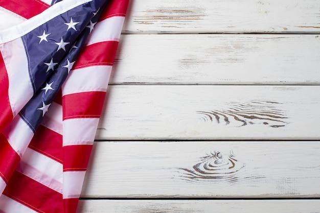 Bandiera americana sgualcita. bandiera degli stati uniti su fondo di legno. bandiera nazionale sul pavimento bianco. unità e orgoglio.