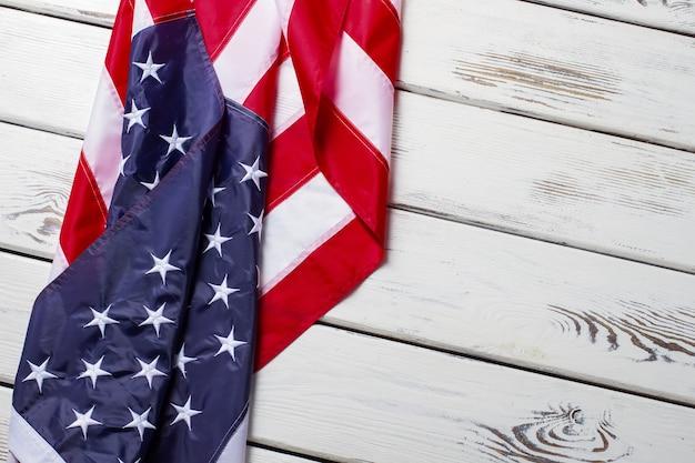 Bandiera usa spiegazzata. bandiera usa su fondo in legno. banner posa su mensola bianca. saluti dalla terra delle opportunità.