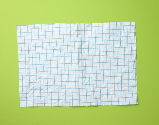 Texture di carta bianca sgualcita in una gabbia, linee blu, superficie verde