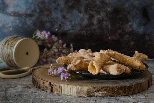Biscotti croccanti chiamati ali d'angelo su una tavola di legno