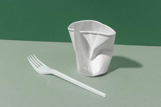 Bicchiere e forchetta di plastica schiacciati
