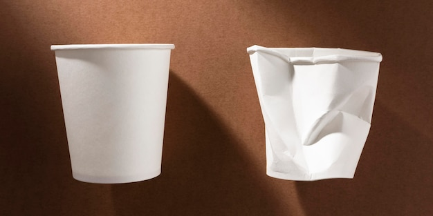 Bicchiere di plastica schiacciato e bicchiere di carta nuovo
