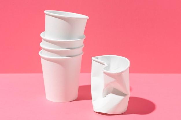 Bicchiere di plastica schiacciato e pila di bicchieri di carta