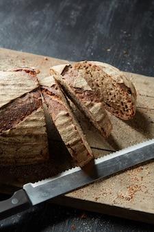 Pane croccante che viene affettato su un vecchio tagliere di legno su uno sfondo scuro