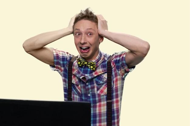 Il ragazzo che piange sta gridando in preda al panico. l'adolescente disperato sta tenendo la sua testa. isolato su sfondo bianco.