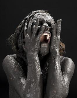 Piangere donna sporca sul muro nero