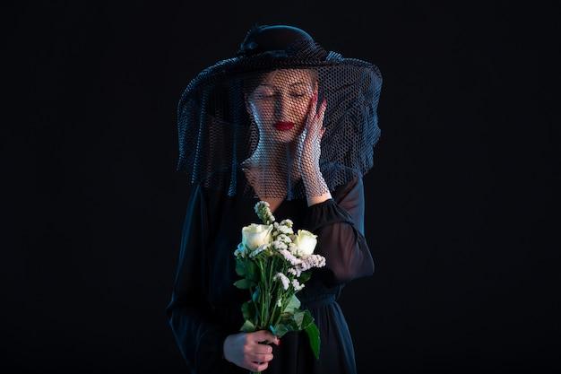 Donna che piange vestita di nero con fiori sul funerale della tristezza della morte nera