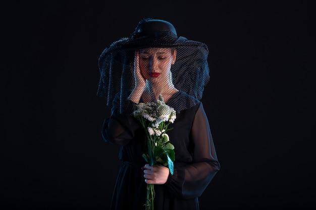 Donna piangente vestita di nero con fiori su nero tristezza morte funerale
