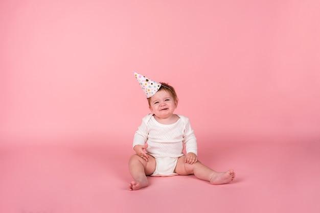 Una ragazza che piange con un body bianco e un cappello da festa