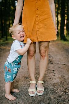 Ragazzino gridante in posa con le gambe della mamma