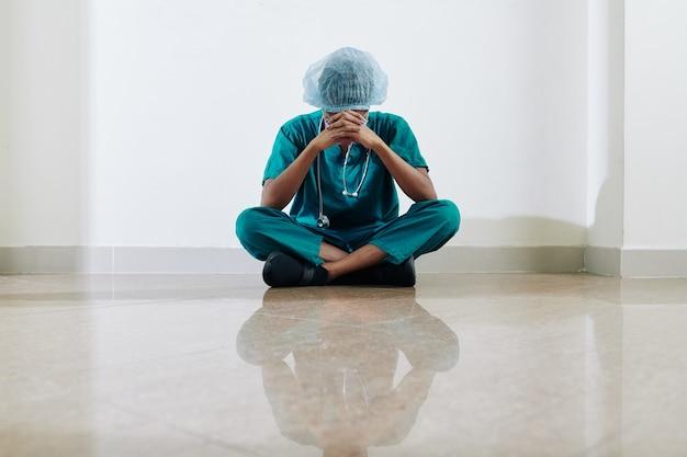 Piangendo infermiera medica stressata e stanca seduta sul pavimento del corridoio dell'ospedale dopo una lunga giornata di lavoro