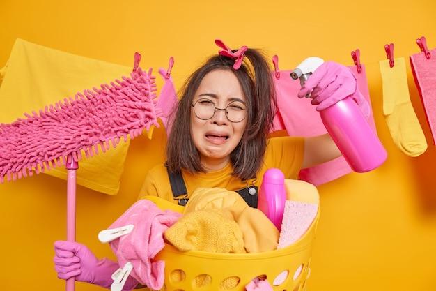 Piangere sconvolta giovane donna asiatica indossa occhiali rotondi tiene detersivo spray e mop si trova vicino al cesto della biancheria frustrato per avere molti lavori domestici