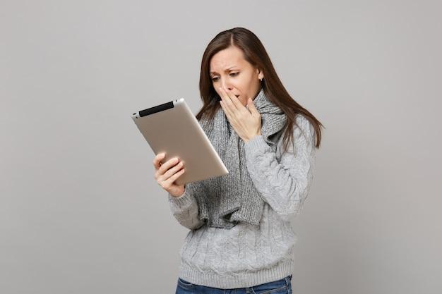 Donna che piange in maglione, sciarpa che copre la bocca con la mano, utilizzando il computer tablet pc isolato su sfondo grigio. stile di vita sano, consulenza sul trattamento online, concetto di stagione fredda. mock up copia spazio.