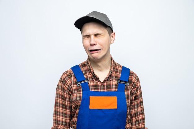 Piangendo giovane addetto alle pulizie che indossa l'uniforme e il berretto tiene uno straccio con un detergente