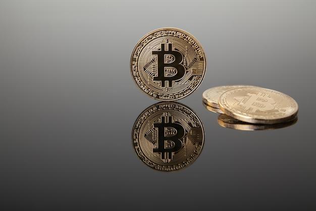 Valuta crittografica. bitcoin oro su vetro grigio con riflessione
