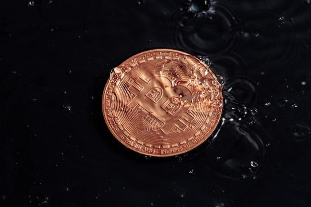 Monete di criptovaluta su uno sfondo scuro. foto macro. gocce di pioggia sulle monete.
