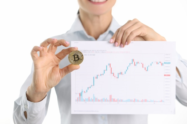 Il consulente di criptovaluta tiene bitcoin e grafico con indicatori finanziari in mano in alto
