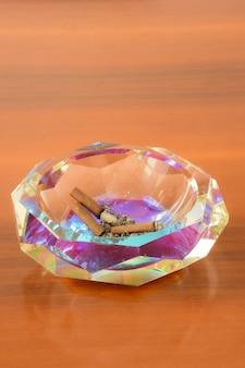 Posacenere di cristallo con sigari estinti su un tavolo di legno