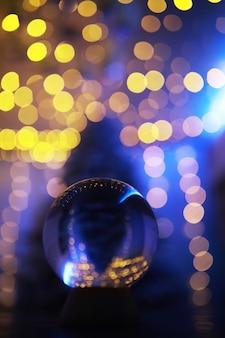 Sfera di cristallo sul pavimento con bokeh, luci dietro. sfera di vetro con luce colorata bokeh, concetto di celebrazione del nuovo anno.