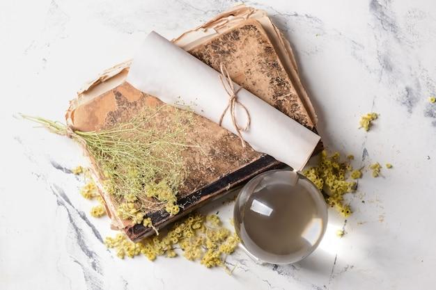 Sfera di cristallo dell'indovino, libro degli incantesimi e pergamena sul tavolo