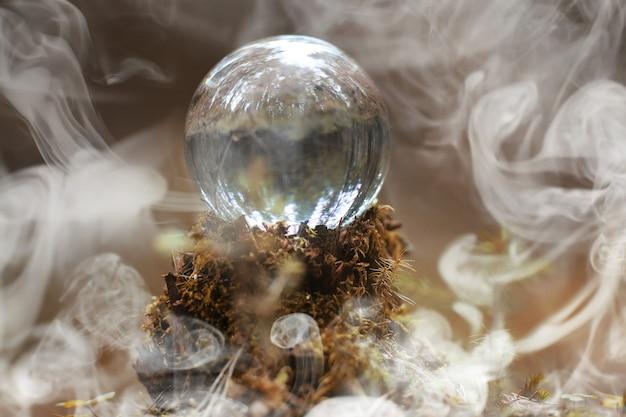 Una sfera di cristallo nel fumo. un accessorio magico nel bosco sul ceppo. palla rituale di streghe e stregoni su un vecchio ceppo marcio ricoperto di muschio.