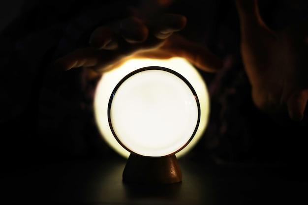 Sfera di cristallo sul tavolo con bokeh, luci dietro. sfera di vetro con luce colorata bokeh, concetto di previsione.