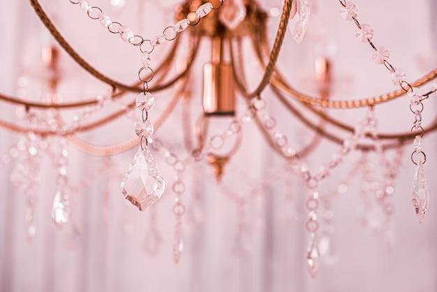 Primo piano del lampadario di cristallo. luce rosa